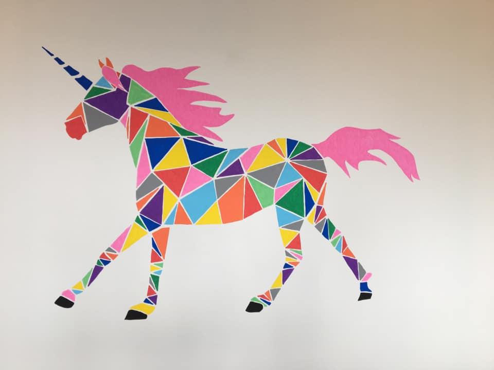Vægdekoration med en farverig enhjørning lavet af mange små trekanter.
